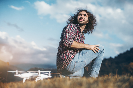 An adult bearded hipster guy with curly hair is looking back while sitting next to his drone on the ground on a sunny day with mountains in a defocused background, prepared to launch his quadcopter Banco de Imagens