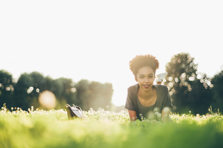 View from the ground level of a sunny glade with beautiful happy African-American girl laying on in the grass with a small bag near her, shallow depth of field with bokeh, copy space area on the left