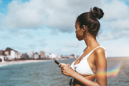 Side view of an exquisite young African-American girl in the swimsuit standing on the observation point near the ocean and thoughtfully looking on the shoreline and beach with smartphone in her hands