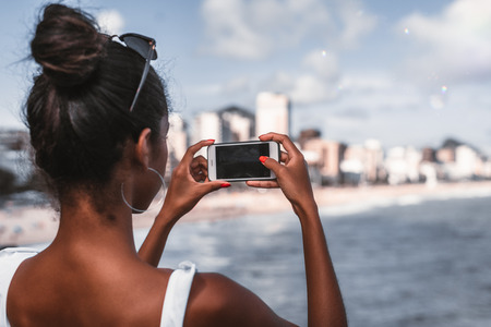 Rear view of African-American female with smartphone taking a photo of the cityscape and coastline; view from behind of a young black girl photographing the beach of the city from an observation point