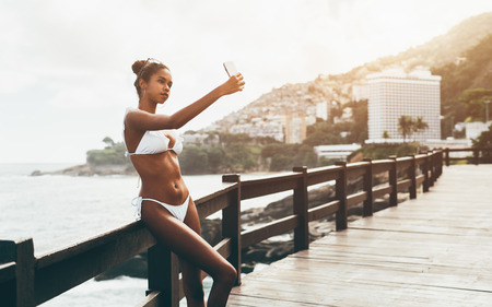 Cute black girl in the swimsuit is taking a selfie outdoors in front of the ocean; young charming Brazilian female is photographing herself on the smartphone while leaning against the wooden fence Stock Photo