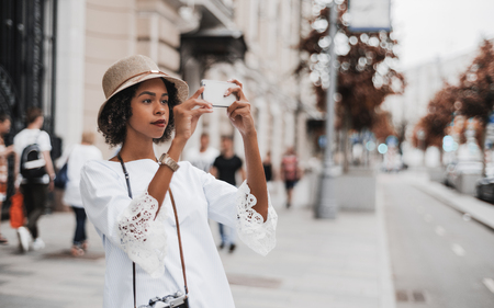 Young lovely black girl with curly Afro hair is taking pics on the street of a European city via the camera of her smartphone while standing on the boulevard with multiple people around
