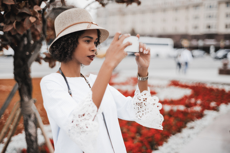 Young exquisite black girl in the hat photographing on the street using the camera of her cellphone; curly African-American female is taking photos outdoors via smartphone, with red flowerbed behind Banco de Imagens
