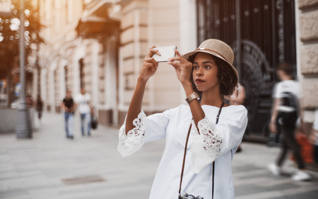 Cute young pensive black girl in the hat with a curly Afro hair is standing outdoors on the busy street and taking photos via cam of her cellphone, with copy space area on the left for text or logo