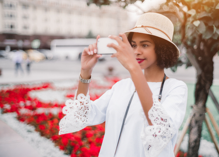 Portrait of a lovely young African-American girl in the hat taking photos of a city while standing outdoors via smartphone, with red flowerbed in the defocused background, shallow depth of field