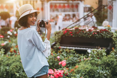 Cheerful ravishing black girl in the hat with vintage photo camera in hands is taking photos of the installation of flower beds on the ground and inside of concert piano in a defocused background Stock Photo