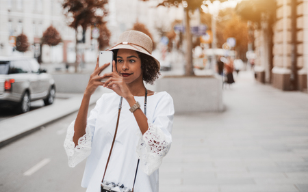 Cute young African-American tourist girl in the hat and a white blouse is taking a photo of a city using camera of her smartphone while standing on the boulevard with copy space place for text message Banco de Imagens