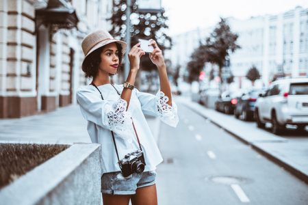 Young adorable black girl in the hat is taking photos of the street using her smartphone, with multiple cars next to her in defocused background and a copy space area on the right for text message