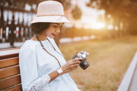 Young exquisite Brazilian female in the hat with a retro film camera in her hands outdoors on the bench; happy black girl with a vintage photo camera is sitting in the park on the wooden bench