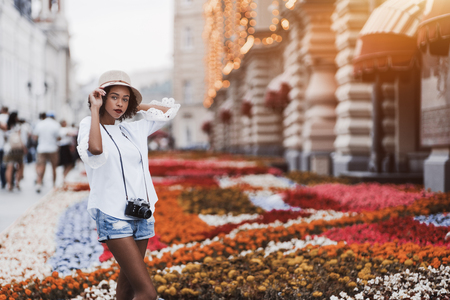 Young exquisite African-American girl with the winsome smile in the hat and with retro film photo camera standing on a street in urban settings with flowerbed behind and copy space area on the right