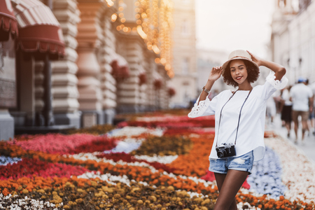 Dainty young African-American tourist girl in hat with curly Afro hair is standing outdoor on the evening street with flowerbed behind her, with copy space area on the right for text or your logo