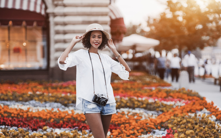 Cheerful African-American girl in hat with vintage photo camera outdoors; smiling cute young Brazilian female on the street with retro film cam on her, the flower bed in a defocused background
