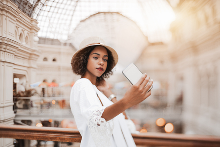 True tilt-shift shot with selective focus: cute young black tourist female in the hat is taking the selfie on her smartphone indoors of a huge shopping mall; selective focus on hand and face Banco de Imagens