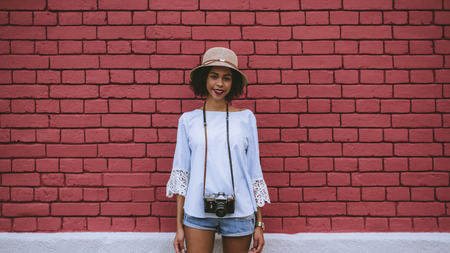 Smiling young black tourist girl with vintage photo camera standing in front of a red brick wall of a summer house; African-American teenage female with the retro film cam next to the brick surface