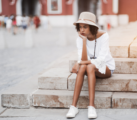 Tired pensive black tourist girl is resting on the concrete step of stone stair outdoors after hours of walking; cute weary African-American girl is reposing on the street stairs after an excursion