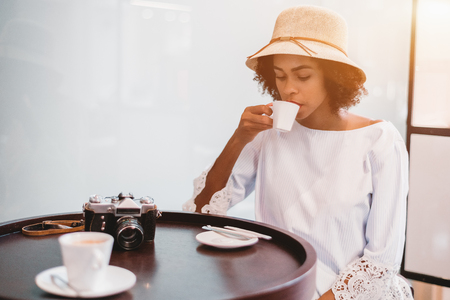 Exquisite African-American tourist girl in the hat is sitting in a cafe and drinking coffee, retro film camera next to her on the table; cute young black curly female in street bar is drinking cocoa