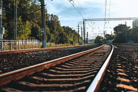 Sunny summer shot of from the ground of railway stretching into the vanishing point; curved railroad track following into distance and bending to the left, with trees, wires, poles, and fence around
