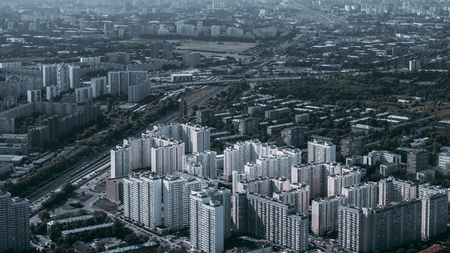 View from a high point of megapolis cityscape with residential mass built-up, road, parks, railroad; urban landscape with multiple apartment houses, highways, and a railway