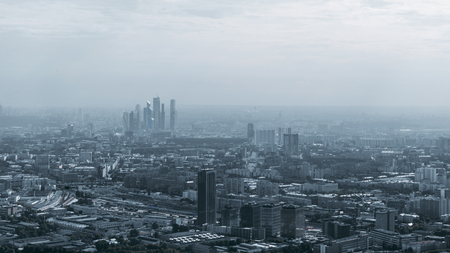 Dark hazy megalopolis cityscape with the group of business skyscrapers in the distance, multiple office and residential houses, highways, parks. Misty, almost invisible horizon Banco de Imagens