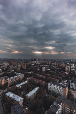Vertical shot from a high point of a dark cityscape with the blocks of flats mass built-up and a thunder sky; view from high above of urban landscape with the residential neighborhood and overcast sky Banco de Imagens