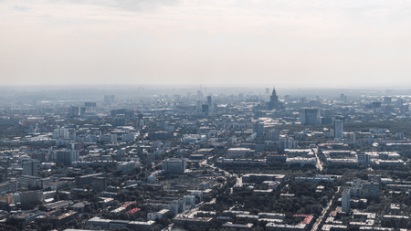 Hazy urban landscape with multiple parks, plenty of residential and manufacture houses, office business buildings, distant horizon; summer sunny megapolis cityscape filmed from a high point