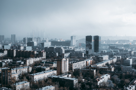Megapolis cityscape from a high point during heavy rain: residential district in the foreground, low dark thunderclouds, rain in a hazy distance, office business skyscrapers in the middle Banco de Imagens