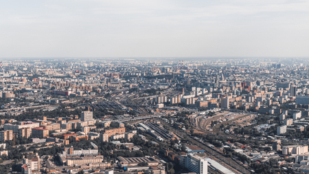 View of sunny megapolis cityscape from high above: huge railroad with multiple tracks, residential districts houses, office buildings and factories, parks and highways, hazy far horizon
