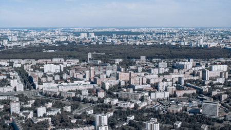 Urban landscape from high above with many residential and manufacture buildings, a highway, park zone and hazy horizon in the distance; metropolis cityscape from a high point with plenty of houses
