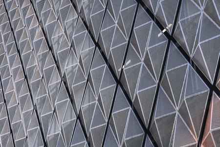 Perspective view of the fragment of the metallic facade of a building in the form of triangles connected to rhombs with solid edges and perforated surfaces, with spaces between rhombs