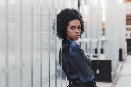 The portrait of beautiful young Brazilian female standing outdoors and leaning against regular glass blocks; charming black girl with curly Afro hair is standing outdoors near the glass installation