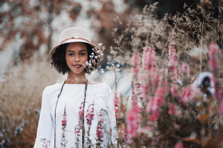 Portrait of a young happy black tourist female in the hat and chemise standing on the summer field, surrounded by colorful native grasses and flowers and looking at the camera; shallow depth of field Banco de Imagens