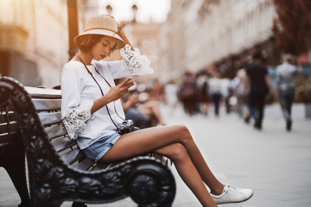 Dainty African-American female in a white chemise and hat and with retro film photo camera is sitting outdoors on a wooden bench of a busy evening street and having chat with family via the smartphone