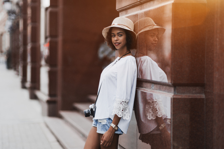 African-American smiling tourist girl in a white chemise and hat with a retro film photo camera is leaning against reflecting marble wall outdoors during the evening; black cheerful female on a street Banco de Imagens