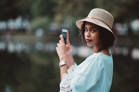 Portrait of exquisite young Brazilian female in the hat and chemise standing next to dark evening pond and taking photos of it using the camera of her smartphone, shallow depth of field, strong bokeh Banco de Imagens