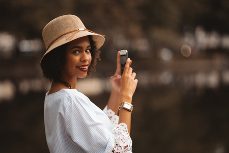 Happy charming young African-American female in the hat and white chemise is standing outdoors near the city pond during the evening and photographing dark water with reflections using her cellphone Banco de Imagens