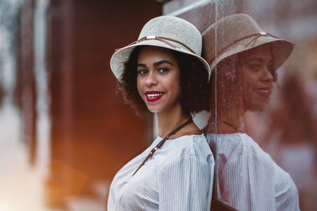 The portrait of a smiling young Brazilian female in the hat, leaning against reflecting marble wall outdoors; cheerful black curly girl on the evening street