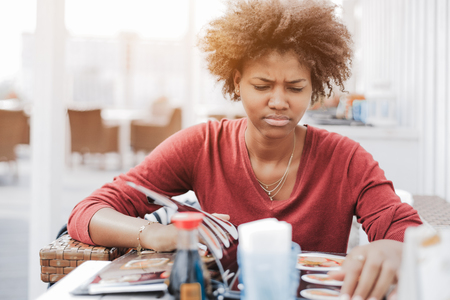 Cute curly African-American girl in street cafe is dissatisfied with an assortment of food in the menu; a young black female is angrily flipping through the menu pages while sitting in a restaurant Stock Photo