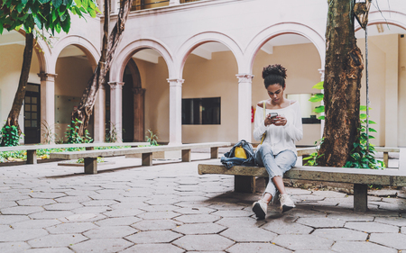 Young cute Brazilian undergraduate girl is sitting in the courtyard of her univercity on the concrete bench and checking her schedule and a hometask using the smartphone, copy space area on the left