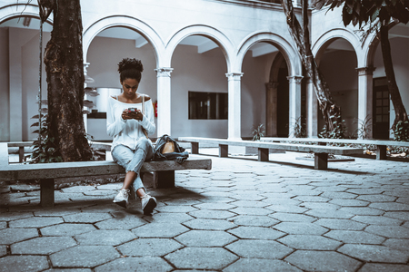 Wide-angle view of a pensive cute African-American female student who is sitting on the concrete bench of her university campus outdoor and messaging with other undergraduates via her smartphone