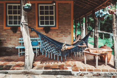 Handsome serious Caucasian male hipster in glasses and with the beard is laying on the knitted hammock outdoors next to his brick country house and having phone conversation with his colleague