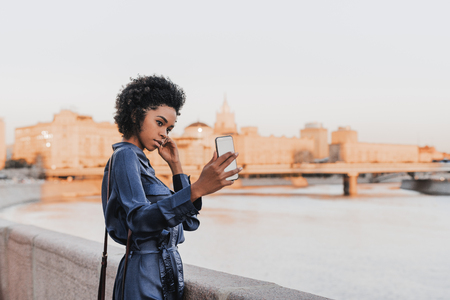 Cute young African-American female tourist in a blue dress is photographing herself near the city river using the smartphone; black charming girl taking selfie via her cellphone next to embankment
