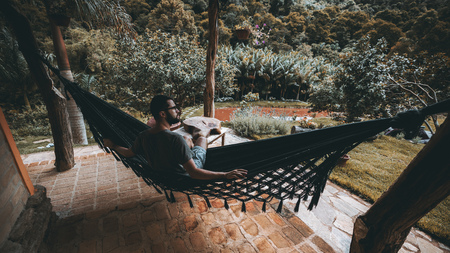 Handsome young bearded man in glasses is thoughtfully looking aside while sitting outdoors of his luxurious summer house in knitted hammock during holidays; rainforest and fishpond in the background