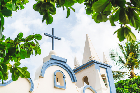 The exterior of a small church Saint Francisco de Assis located in state Bahia of Brazil, in the resort Praia do Forte; with blue wooden cross on the top, the chapel with the bell and frame of leaves