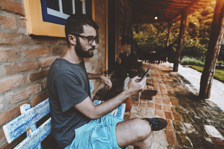 Bearded handsome serious hipster guy in glasses, t-shirt, and shorts is sitting outdoors on the terrace of his summer cottage on a blue wooden bench and messaging via smartphone during his vacation