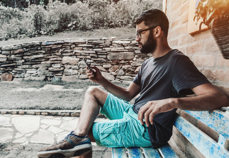 Serious adonic hipster guy with the beard and in glasses is sitting on a bluish grungy wooden bench outdoors next to the brick wall and having a video call with his friend via the smartphone Banco de Imagens