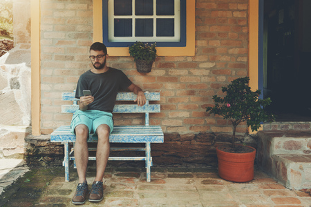 Pensive young bearded hipster man is sitting on the bluish wooden bench on the verandah of a fancy street cafe or a summer house and texting message to his colleagues in a group chat of a messenger Banco de Imagens