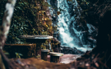 Magical dark forsaken place in the rainforest with ancient stone table and backless stools near it, waterfall in a defocused background; shallow depth of field, the jungle of Ibitipoca, Brazil Banco de Imagens