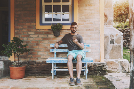 Pensive young man with the beard and in glasses is checking incoming message on his cell phone while sitting on the bluish wooden bench under the window on the verandah of his summer residence
