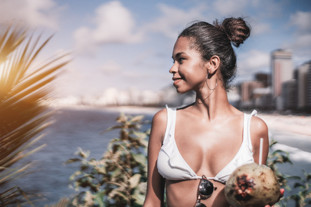 Portrait of young charming Brazilian female standing not far from the coastline with coconut and looking aside, with copy space place for text, your logo or advertising message on the left, sunny day Standard-Bild