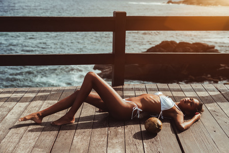 Sexy svelte young African-American girl in the swimsuit is laying on the wooden pier of a tropical resort with the coconut next to her; fence, ocean water and rocks behind her in the background
